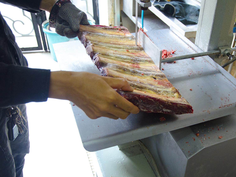 thợ đang sùng máy cắt xương bò Úc đông lạnh